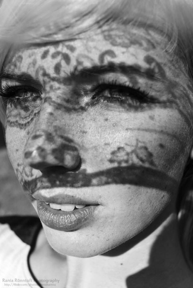 光と影の芸術:顔にタトゥーの女性