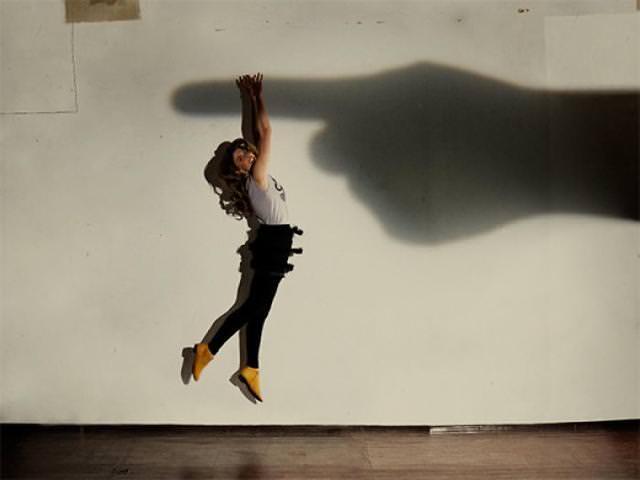 光と影の芸術:巨人の指にぶら下がる女性