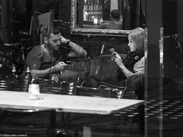 お互いに無関心で、それぞれスマートフォンに夢中になっているカップル