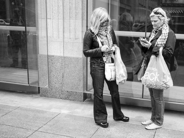 向い合ってスマートフォンを操作する女性二人