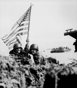 ほふく前進で星条旗を掲げる兵士たち