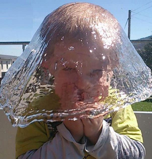 決定的瞬間:水で出来た帽子をかぶる少年