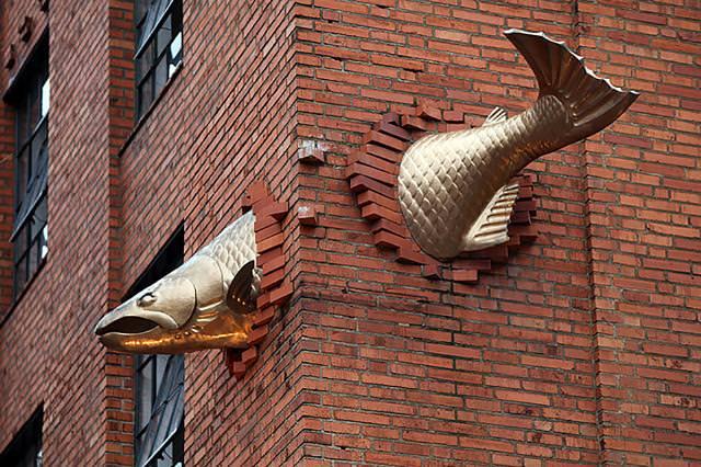 現代アートのオブジェ:巨大な魚がビルに突き刺さる!