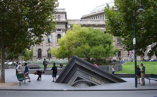 現代アートのオブジェ:地面の中に沈んでいく建物