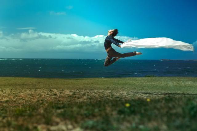 海の見える草原で、大空に向かってジャンプ!