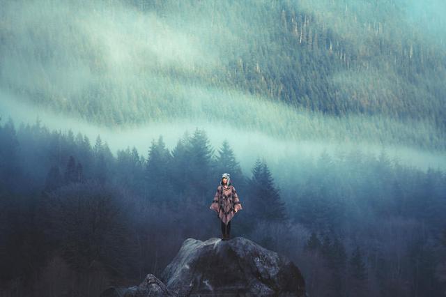 山頂の岩の上で立つ蛮勇な女性