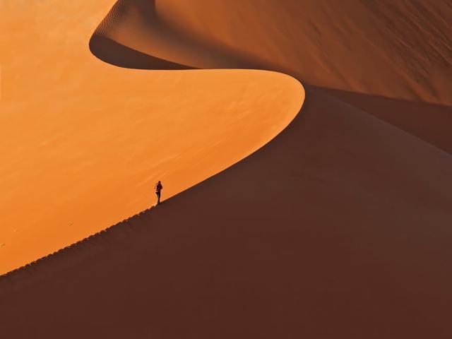 見渡すかぎりの砂丘を歩く人