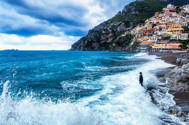 波打ち際に立って海を眺める女性(イタリア-ポジターノ)
