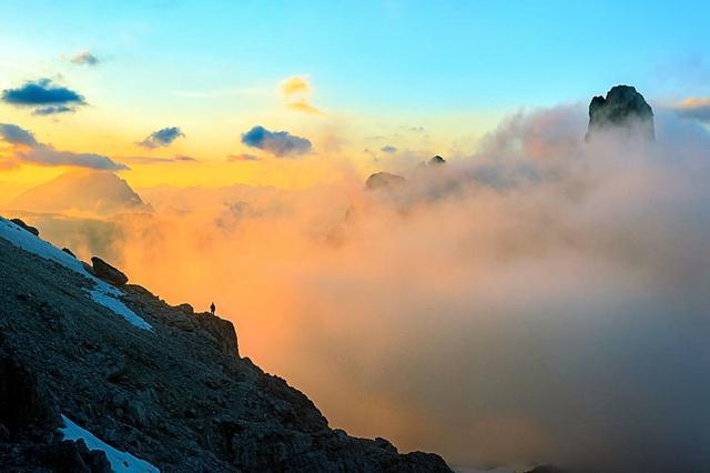 山の岩場に立ち、雲を眺める人(イタリア-アルプス山脈ドロミテ)