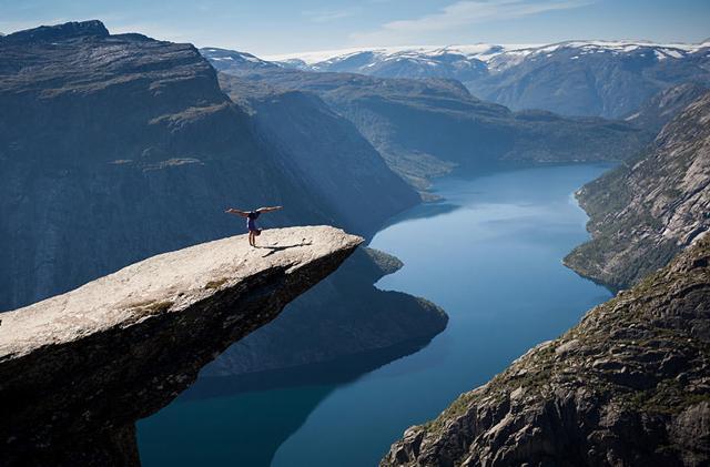 突き出した岩の上で逆立ちをする女性(ノルウェー-Trolltunga rock)