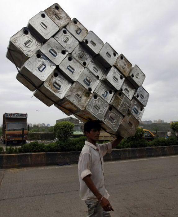 なんと26個もの石油缶を、頭の上に乗せて運ぶ男性