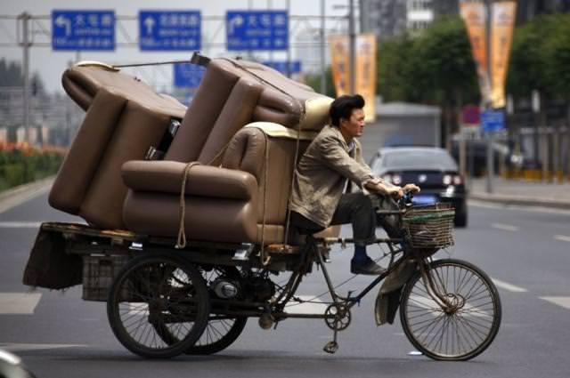 ソファー4つを自転車に乗せ、一人で運ぶ人