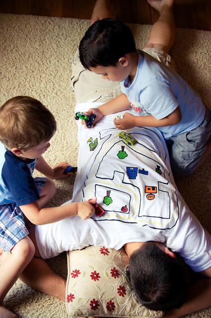 育児のアイディア:寝ている自分の背中で子供を遊ばせるイクメンパパ