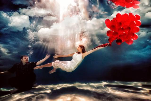 カップルの水中写真:飛び去ろうとしている婚約者に、手を差し伸べる男性