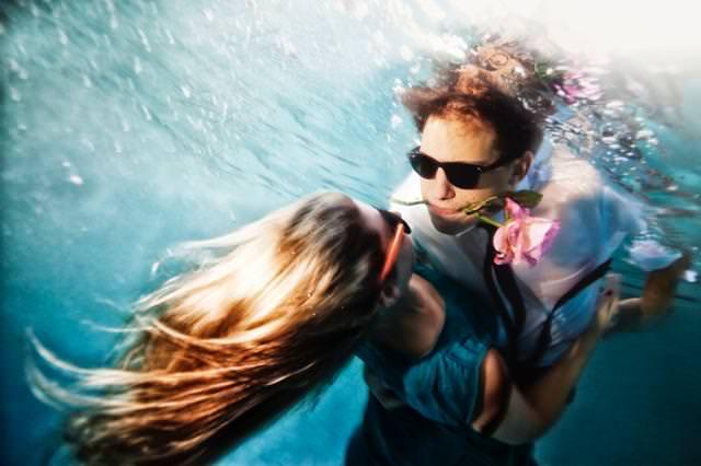 カップルの水中写真:口に薔薇をくわえて彼女を抱きしめる男性