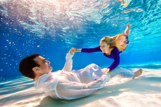 カップルの水中写真:水中で両手をつないでラブラブ