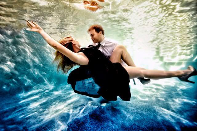 カップルの水中写真:彼女の全身を抱きかかえる彼氏