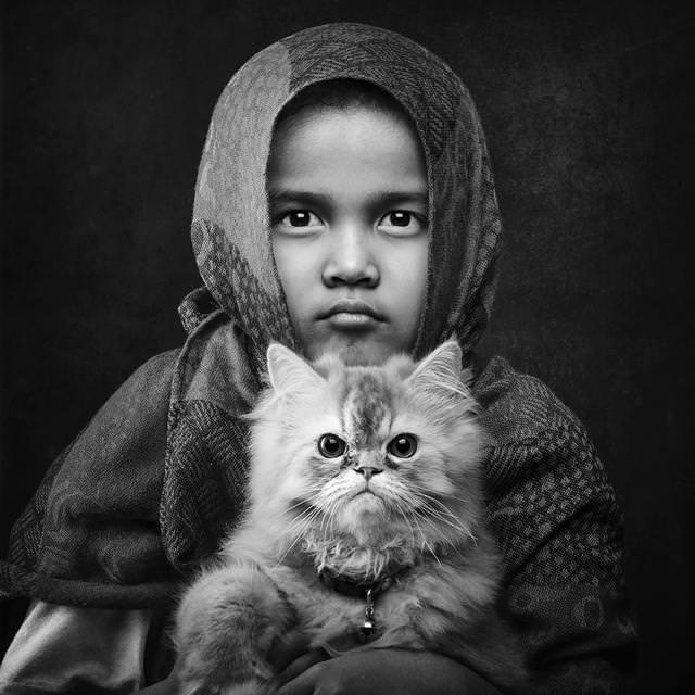 猫を抱きかかえる健気な少女