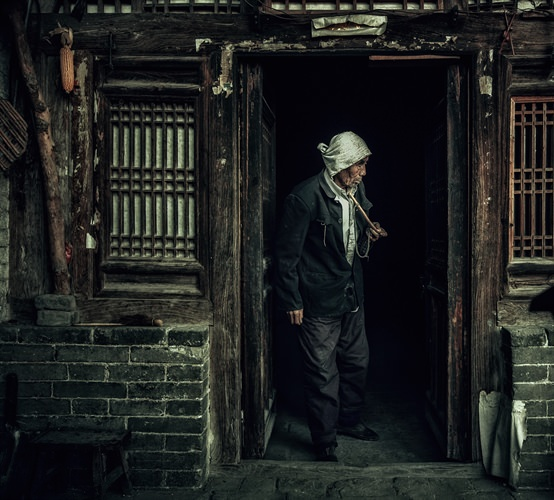 古い家屋から出てくる老人