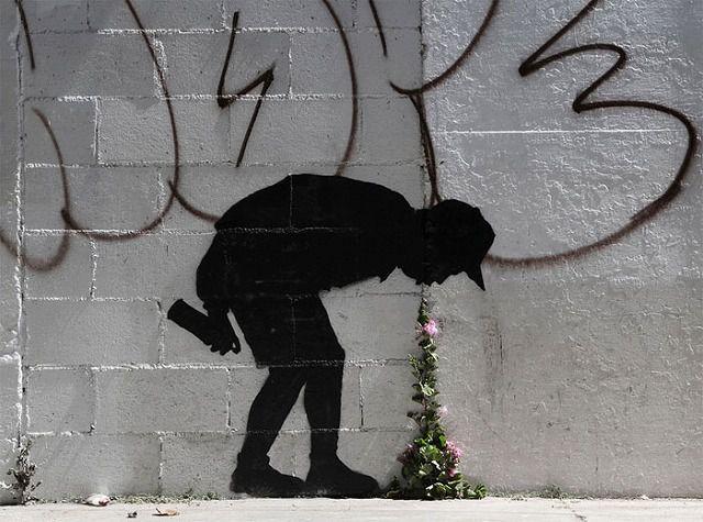 上手いストリートアート:少年の影が口からゲロ