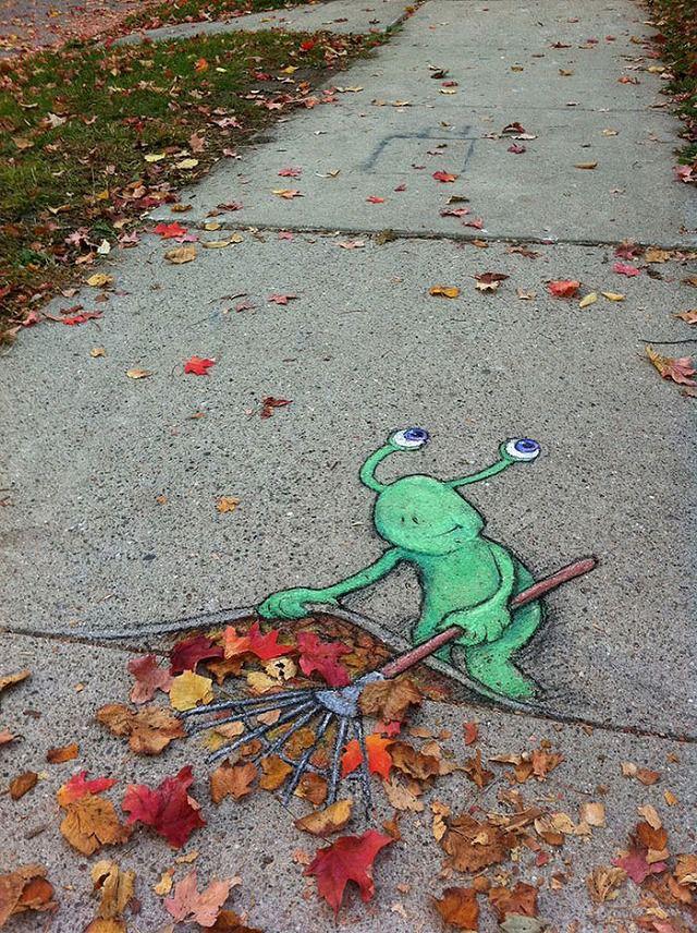 上手く地面に描かれたストリートアート:落ち葉を掃除するモンスター