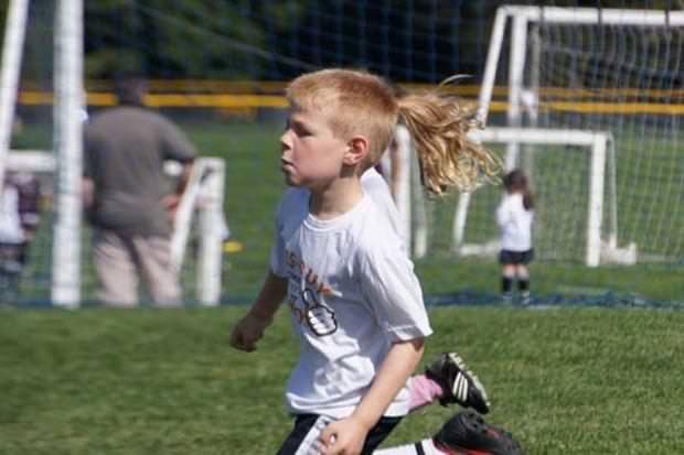 目の錯覚の面白写真:スポーツカットでポニーテールを結んでいるサッカー少年