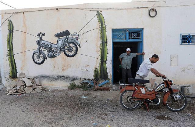 スペイン人の描いたストリートアート:有刺鉄線で宙吊りにされたバイク