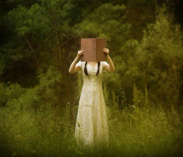 本で顔を隠すツインテールの女性