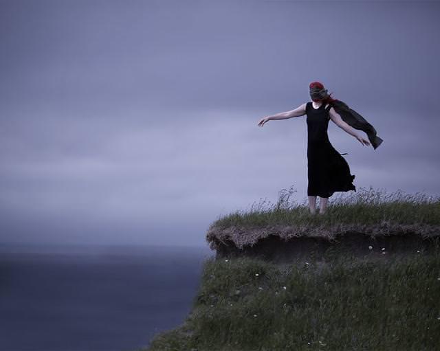 目隠しをしながら、断崖絶壁に立つ女性