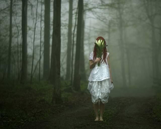 森を裸足で歩きながら、葉っぱで顔を隠す女性