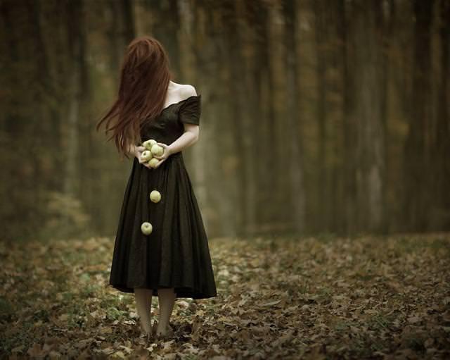 森の中、髪の毛で顔を隠す女性