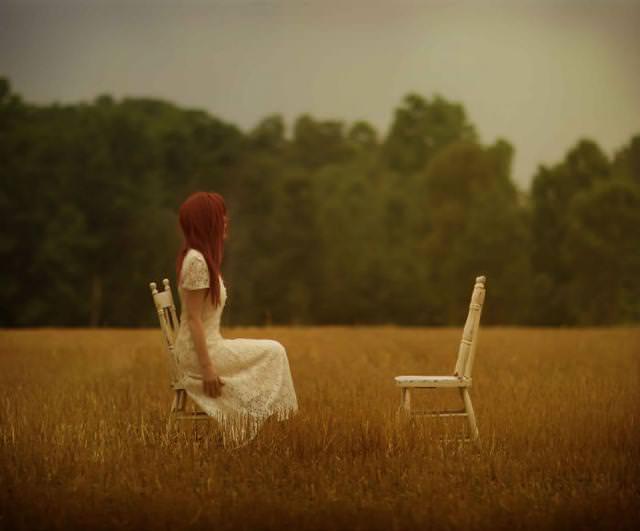 誰も座っていないイスと向き合う女性