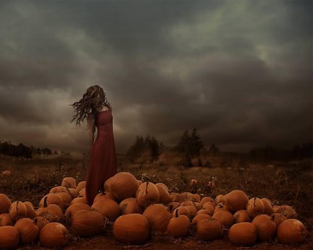 雨雲の下、農作物と一緒に佇む女性
