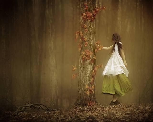 森で木に話しかける女性