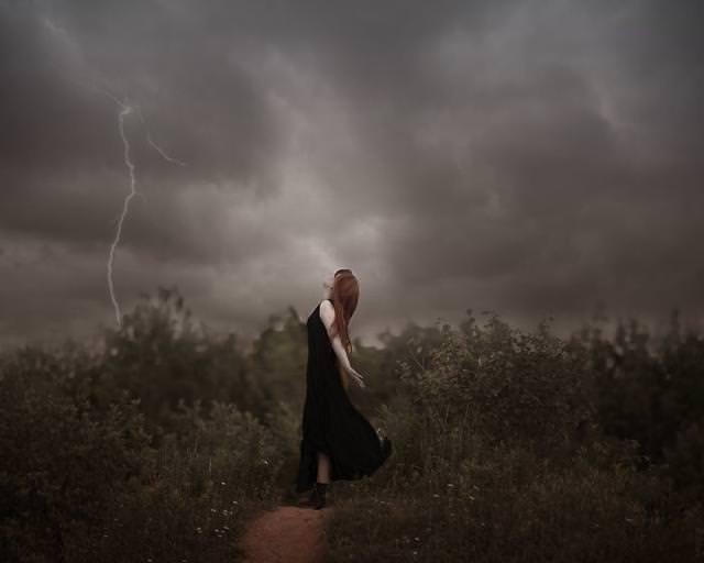 稲妻が鳴り響く草原で、空を仰ぎ見る女性