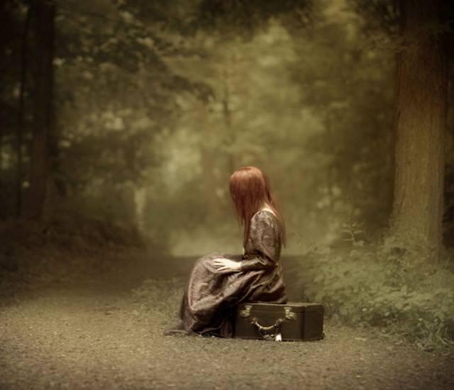 森の中で、荷物に腰掛けて考えこむ女性