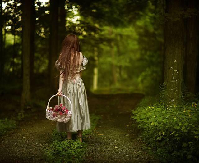 花かごを持って、森の中を歩く女性